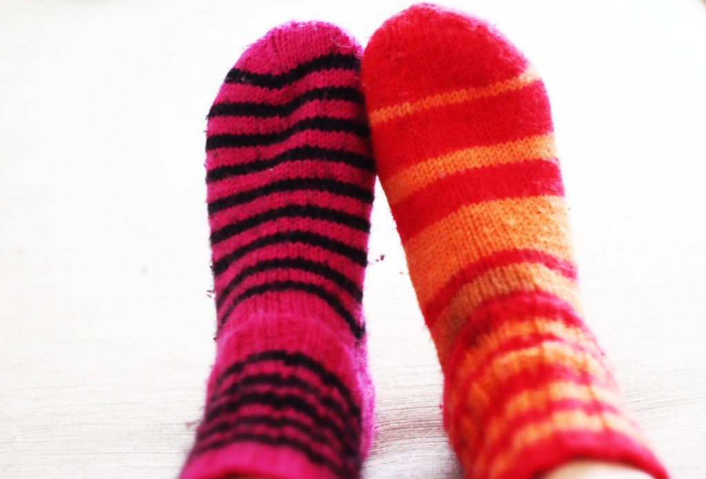 Hengailla eripari villasukat jalassa sohvalla