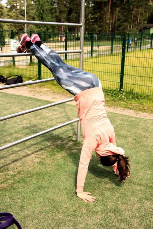 Hyvä tapa lähteä harjoittelemaan käsilläseisontapunnerrusta on käyttää apuna puolapuita. Nosta jalat telineelle ja punnerra.