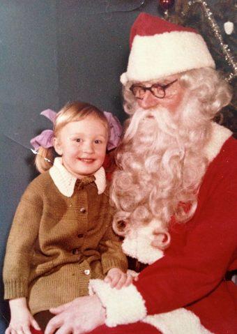 Pikku-Hanna Stockmannin joulupukin sylissä. Päällä on alli-Mummin kutoma mekko