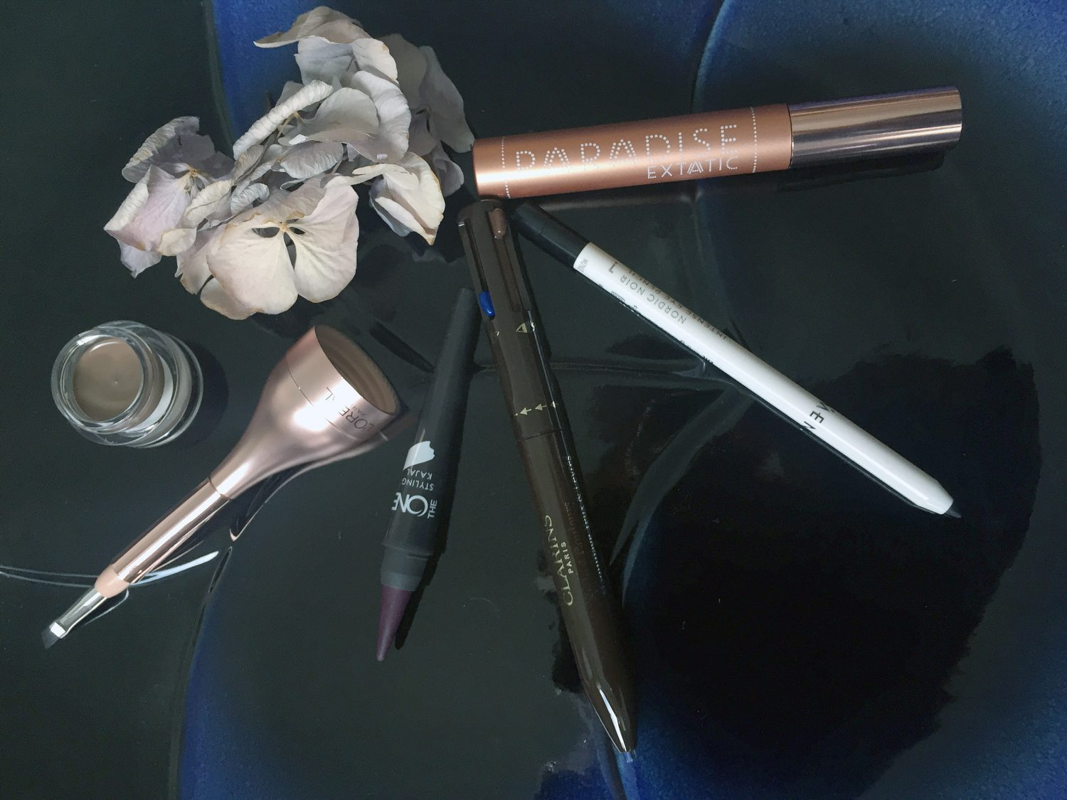 Vasemma L'Oréal Paris Paradise Pomade Extatic -kulmaväri sävy 103 Chatain, Oriflame The One Styling Kajal -rajausväri sävy Purple Intensity, Clarins Stylo 4 Color All-in-One Eyes & Lips -kynä, Lumene Nordic Noir Intense Eye Pencil -rajausväri ja L'Oréal Paris Paradise Extatic -ripsiväri.